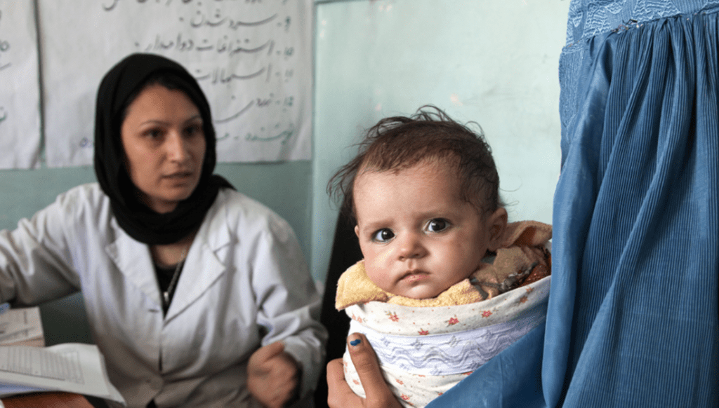 Baby and mother at a medical clinic in Afghanistan. Photo by Graham Crouch/World Bank, courtesy of Flickr Creative Commons.