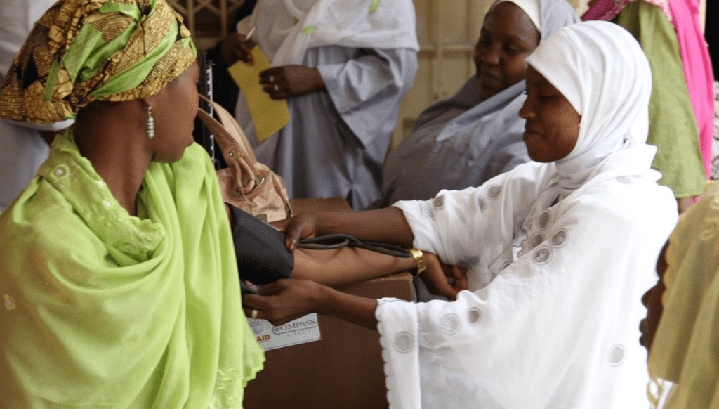 A health worker takes the blood pressure of a woman at a family planning and maternity clinic in Kano, Nigeria. Photo by Bonnie Gillespie, courtesy of Photoshare.