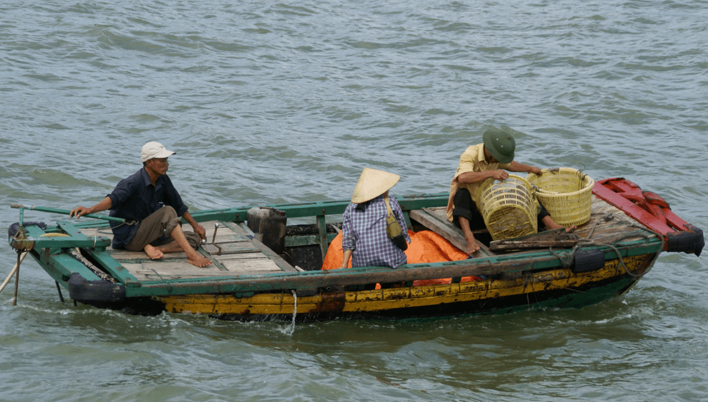 People ride in a boat in Vietnam. Photo by Patrik M. Loeff, courtesy of Flickr Creative Commons.