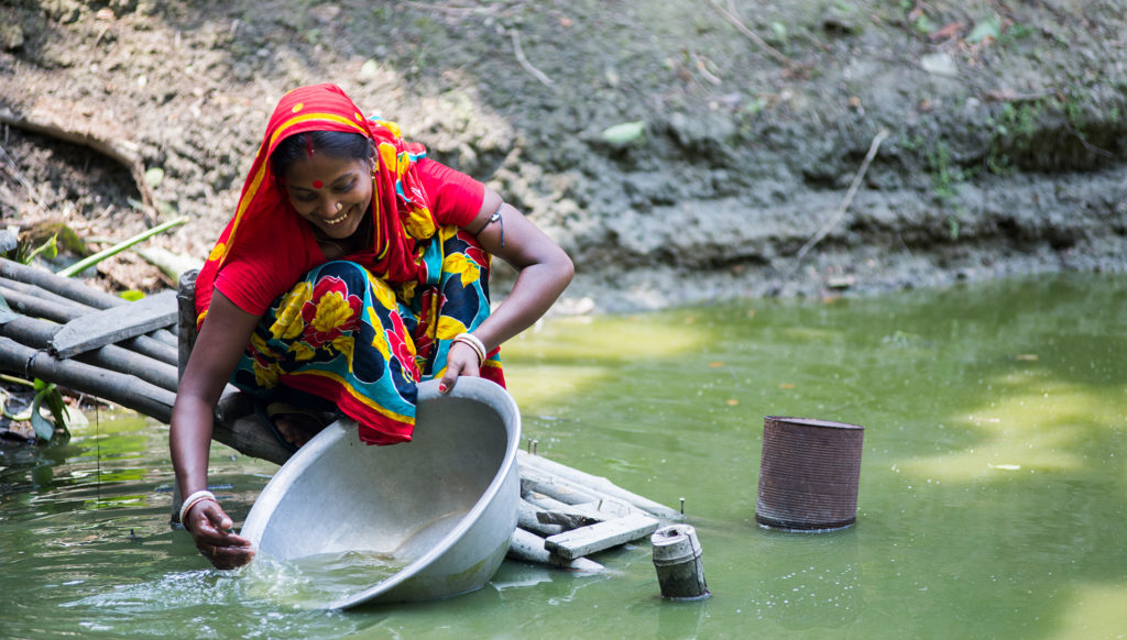 Woman at a pond in Bangladesh. Photo by WorldFish, courtesy of Flickr Creative Commons.